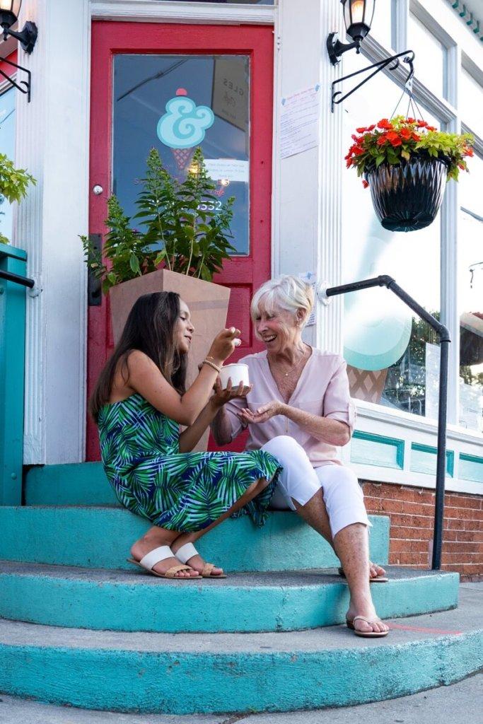 two women enjoying ice cream on teal stairs