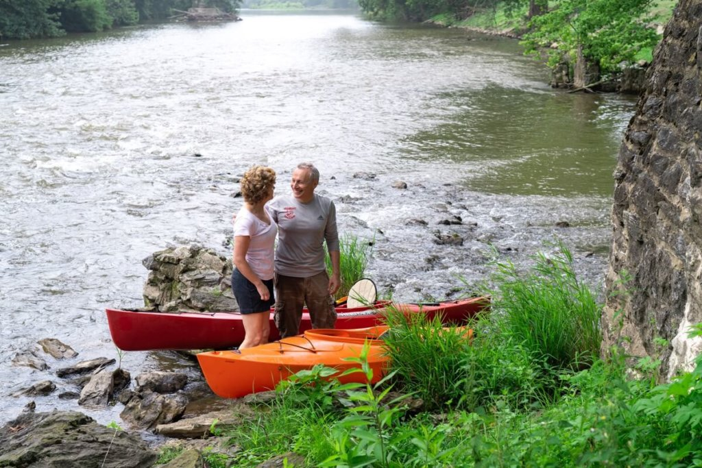 older man and woman standing with kayaks creekside