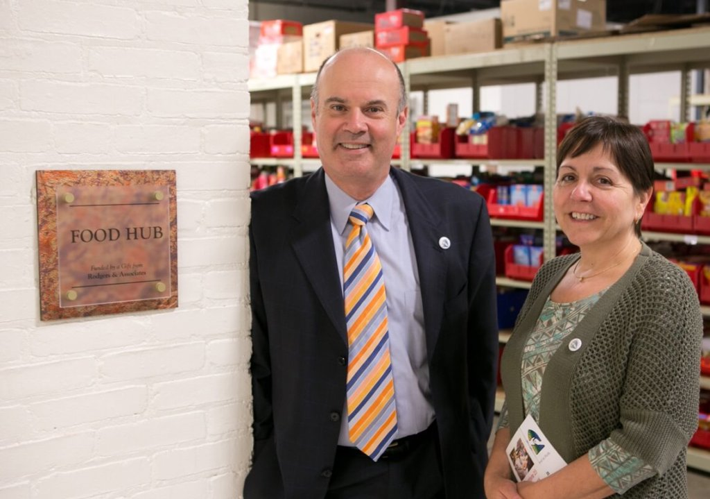 Rick and Jessica standing next to their plaque at the Food Hub